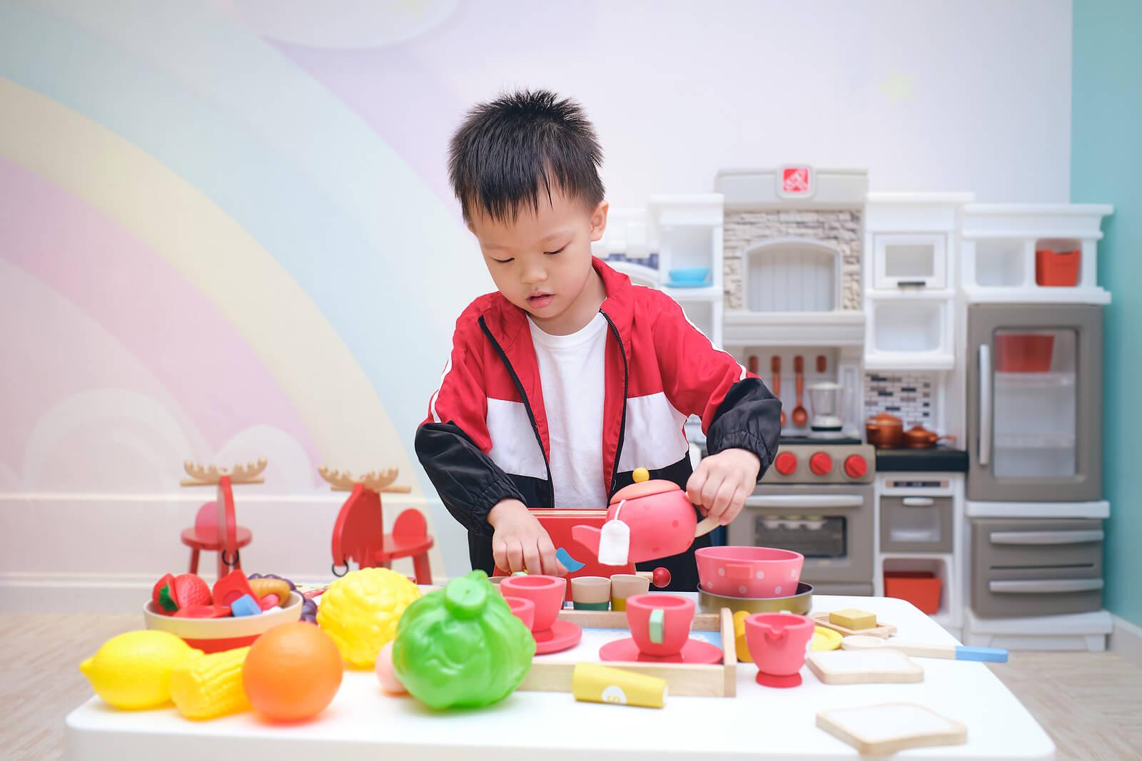 Niño jugando a servir el té para prevenir la violencia de género.