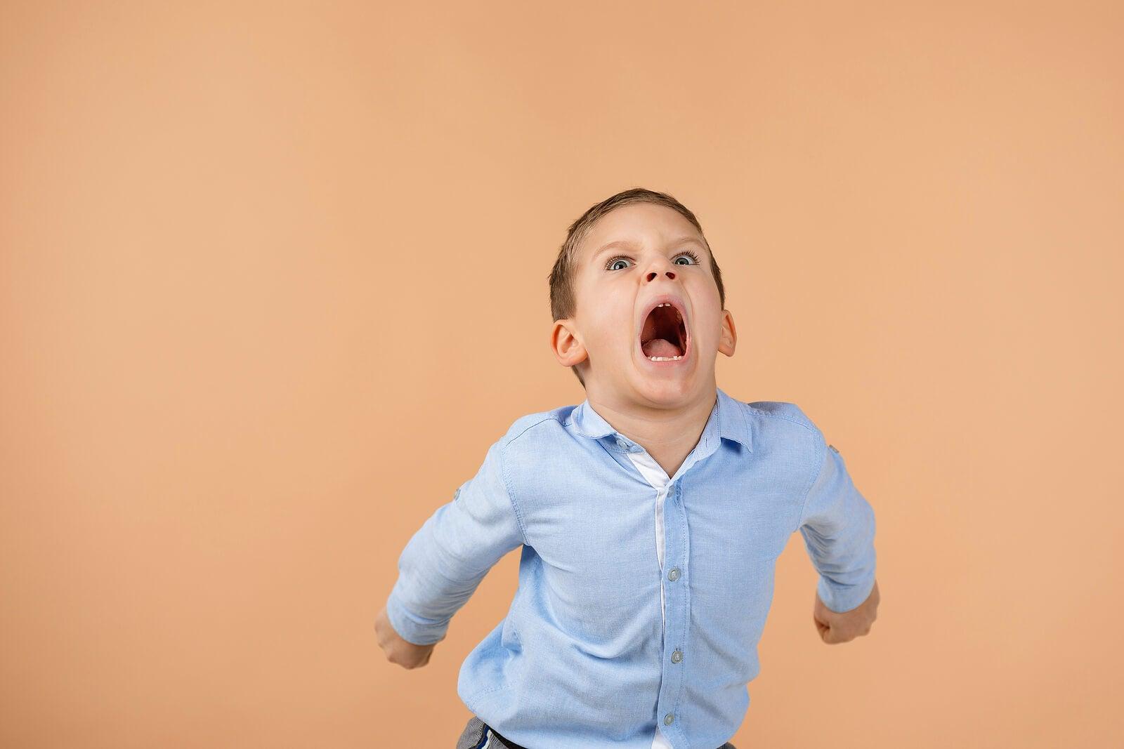 Niño gritando lleno de ira.