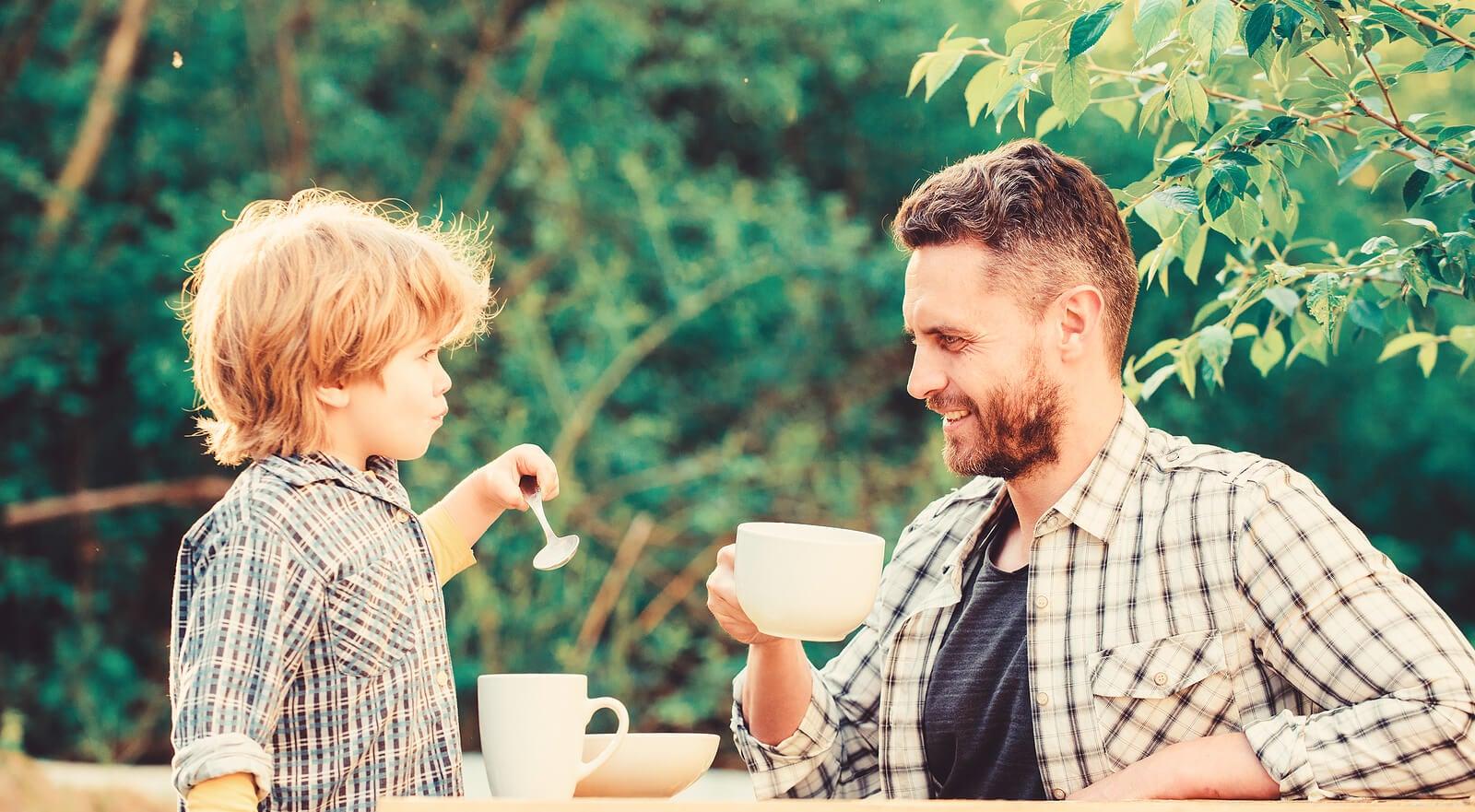 Padre a hijo merendando juntos para enseñarle buenos modales.