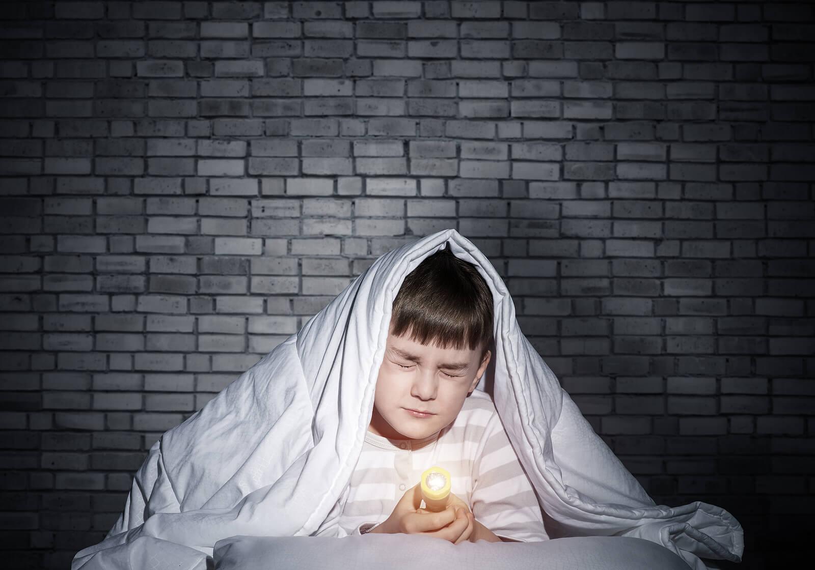 Niño con miedo a la oscuridad con una vela en la cama.