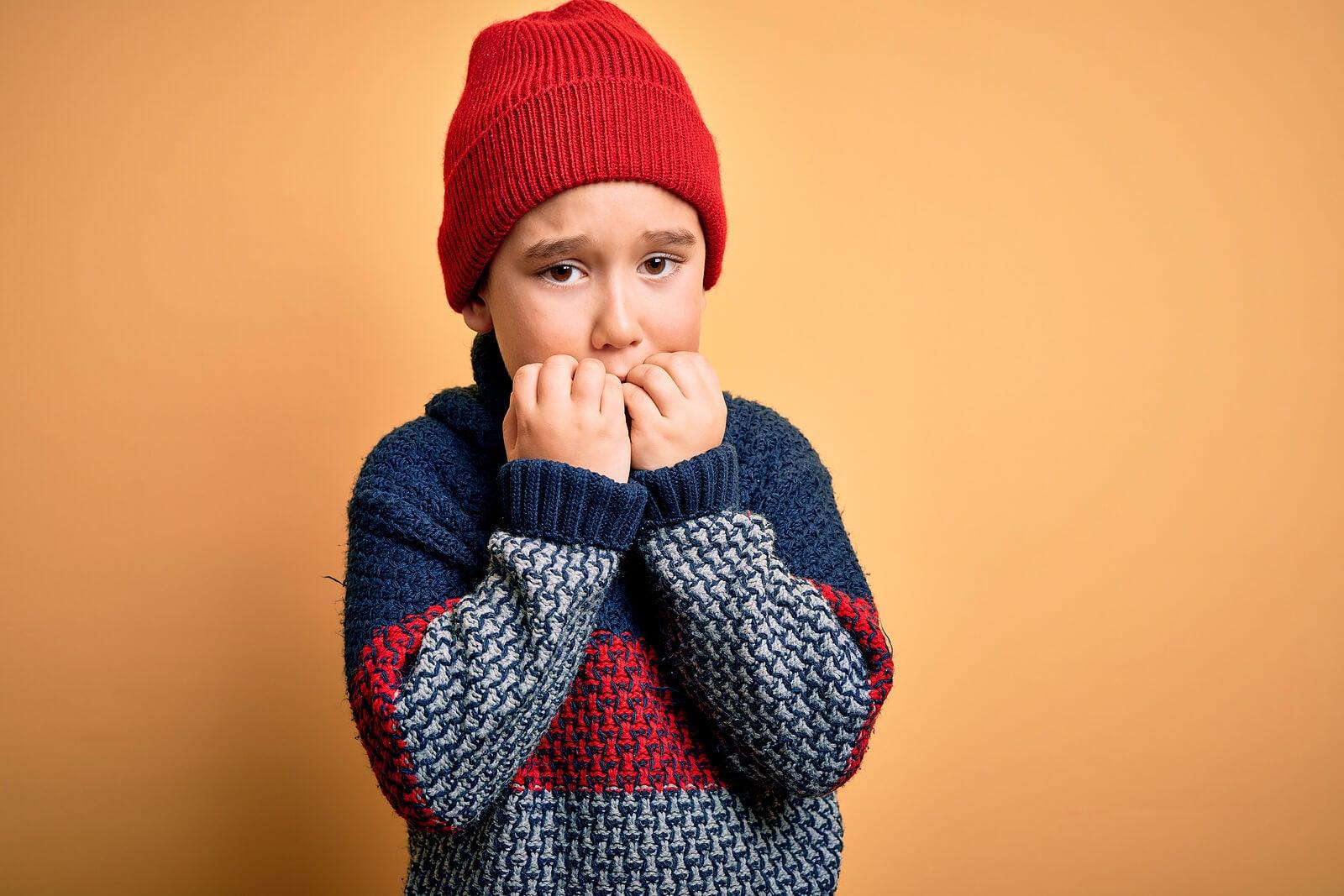 Niño mordiéndose las uñas porque tiene miedo, una de las formas de detectar fobias.