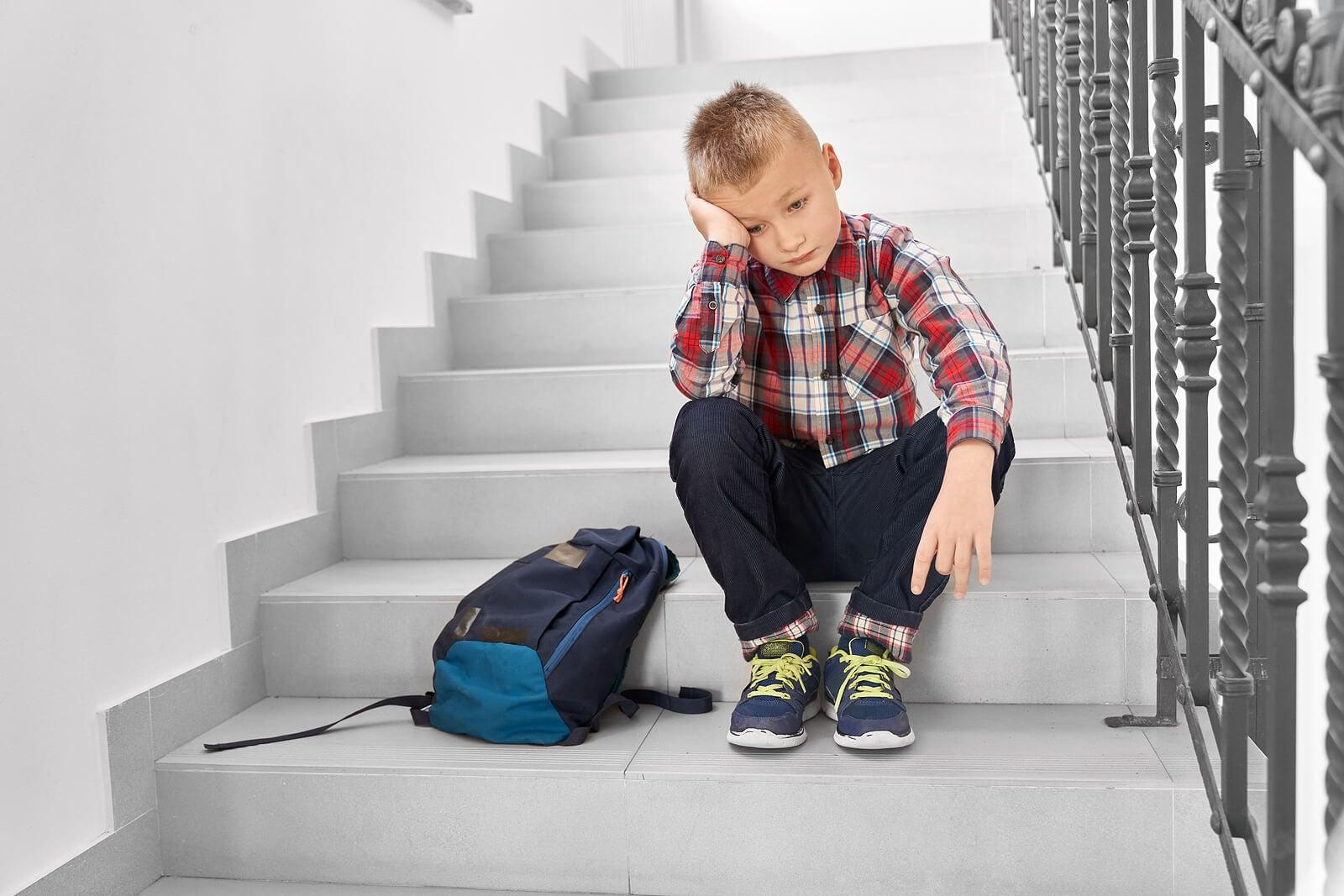Niño sentado en las escaleras de casa pensando en que tiene que ir al colegio pero sufre fobia escolar.