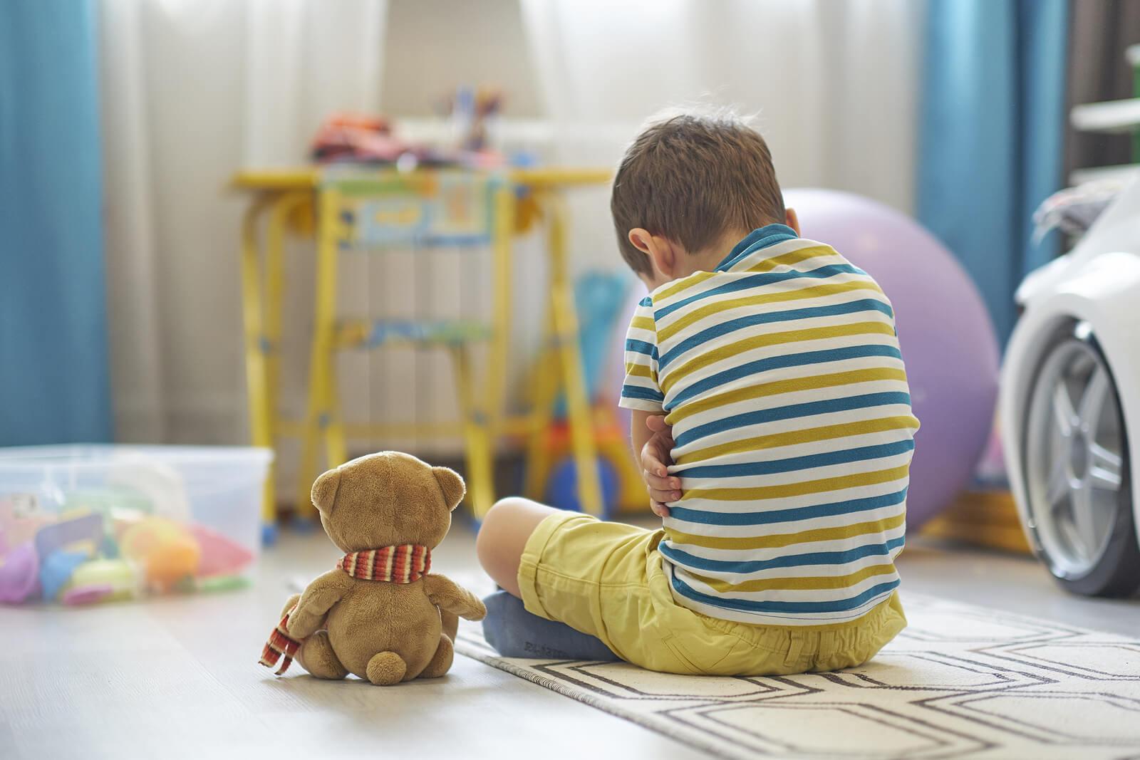 Niño sentado en el suelo pasando por un trastorno de estrés postraumático.