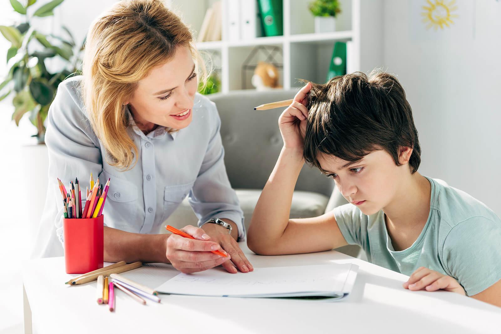 Niño trabajando con su logopeda porque tiene dislexia infantil.