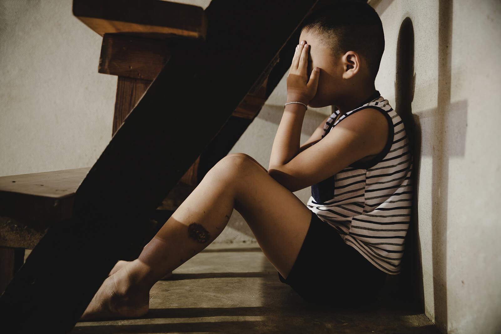 Niño triste debido al abandono paterno.
