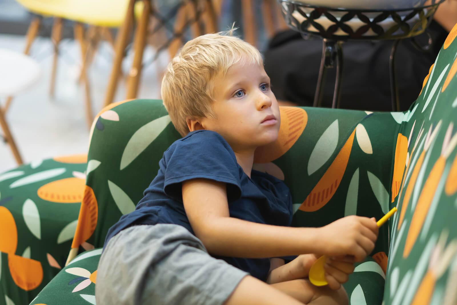 Niño en el sofá pensando las consecuencias de su mala conducta.