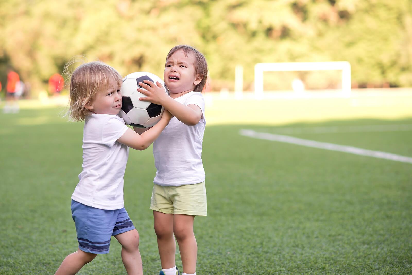 Niños peleando por un balón de fútbol.