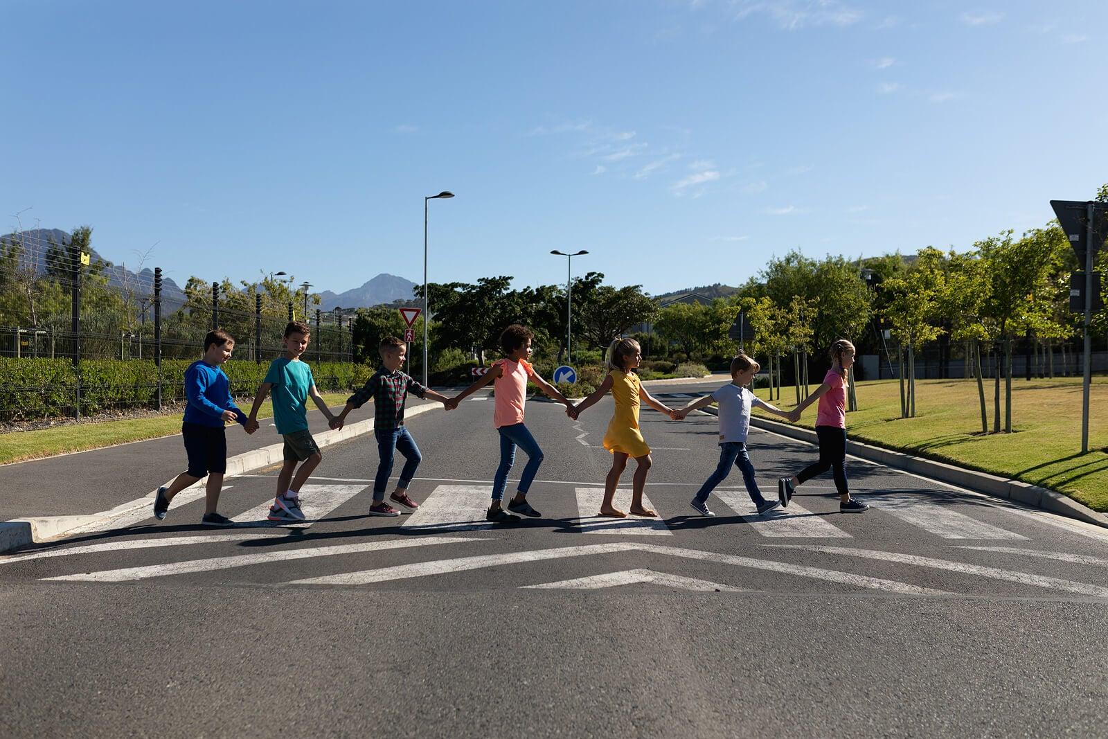 Niños de la mano cruzando un paso de peatones.