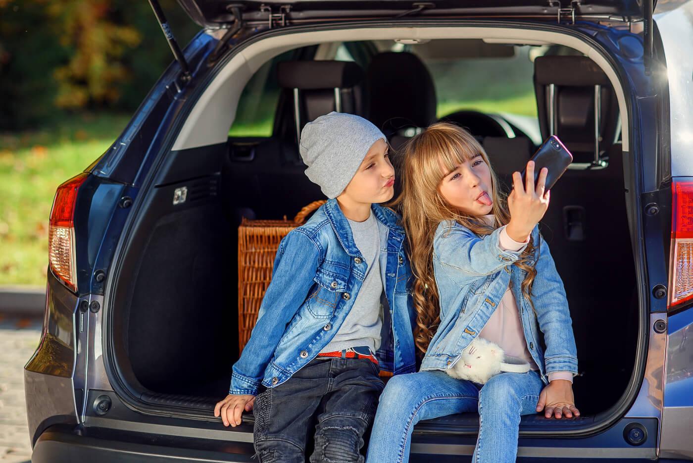 Niños entre los 10 y los 12 años haciéndose un selfie en el coche.