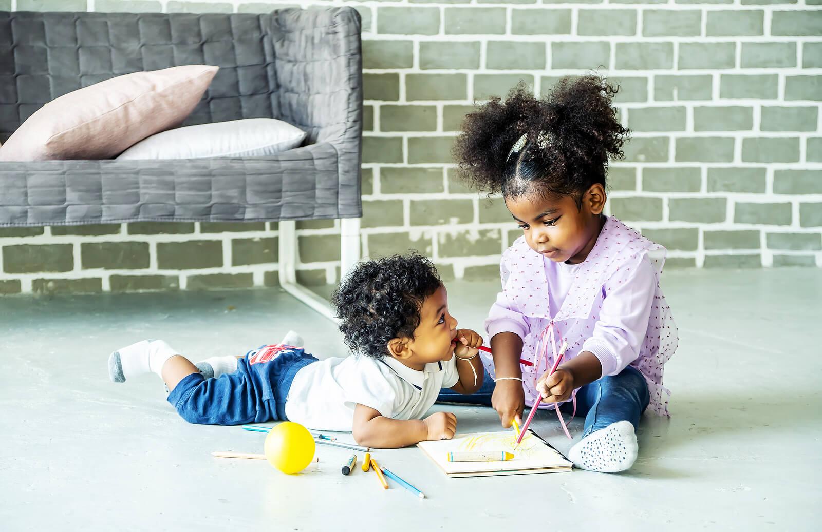 Niños hermanos haciendo manualidades en casa.