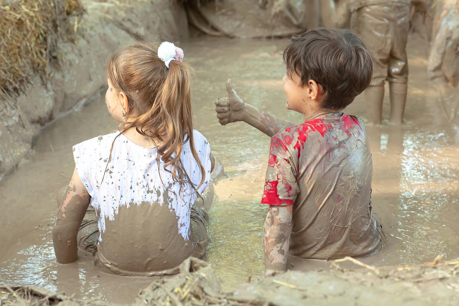 Niños en una piscina de barro aprendiendo a soltar el control.