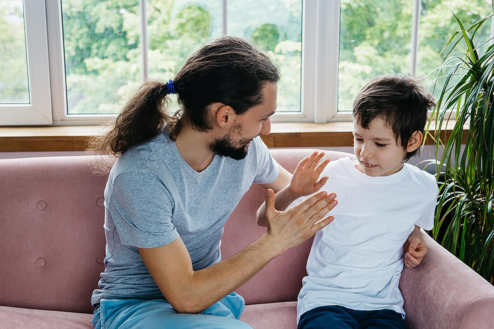 Padre chocando la mano con su hijo con síndrome de Marfan.