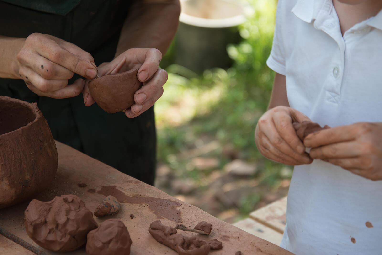 Padre e hijo haciendo figuras con barro.