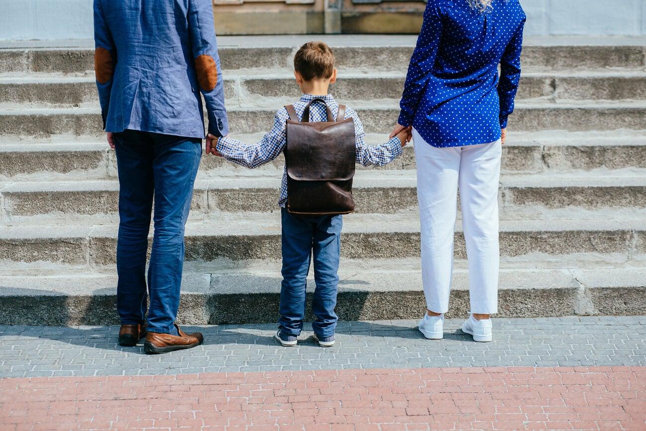 Padres acompañando a su hijo a la escuela.