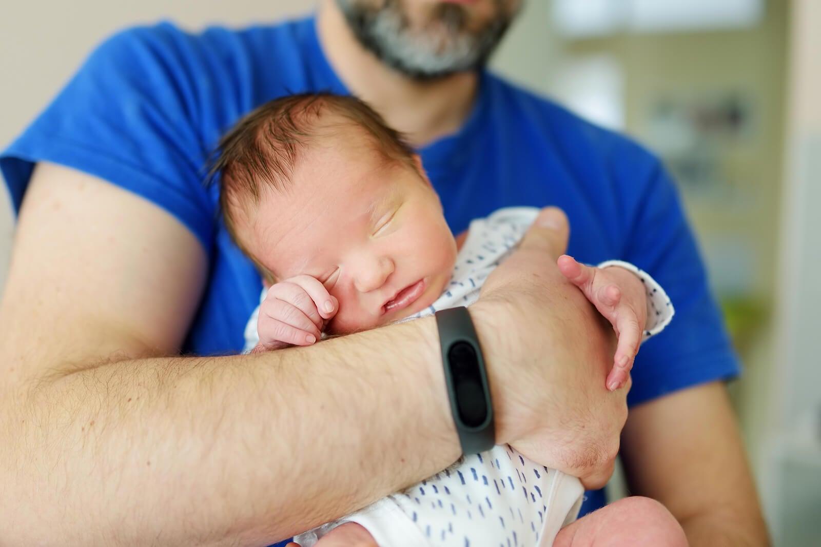 Papá con su bebé recién nacido en brazos.