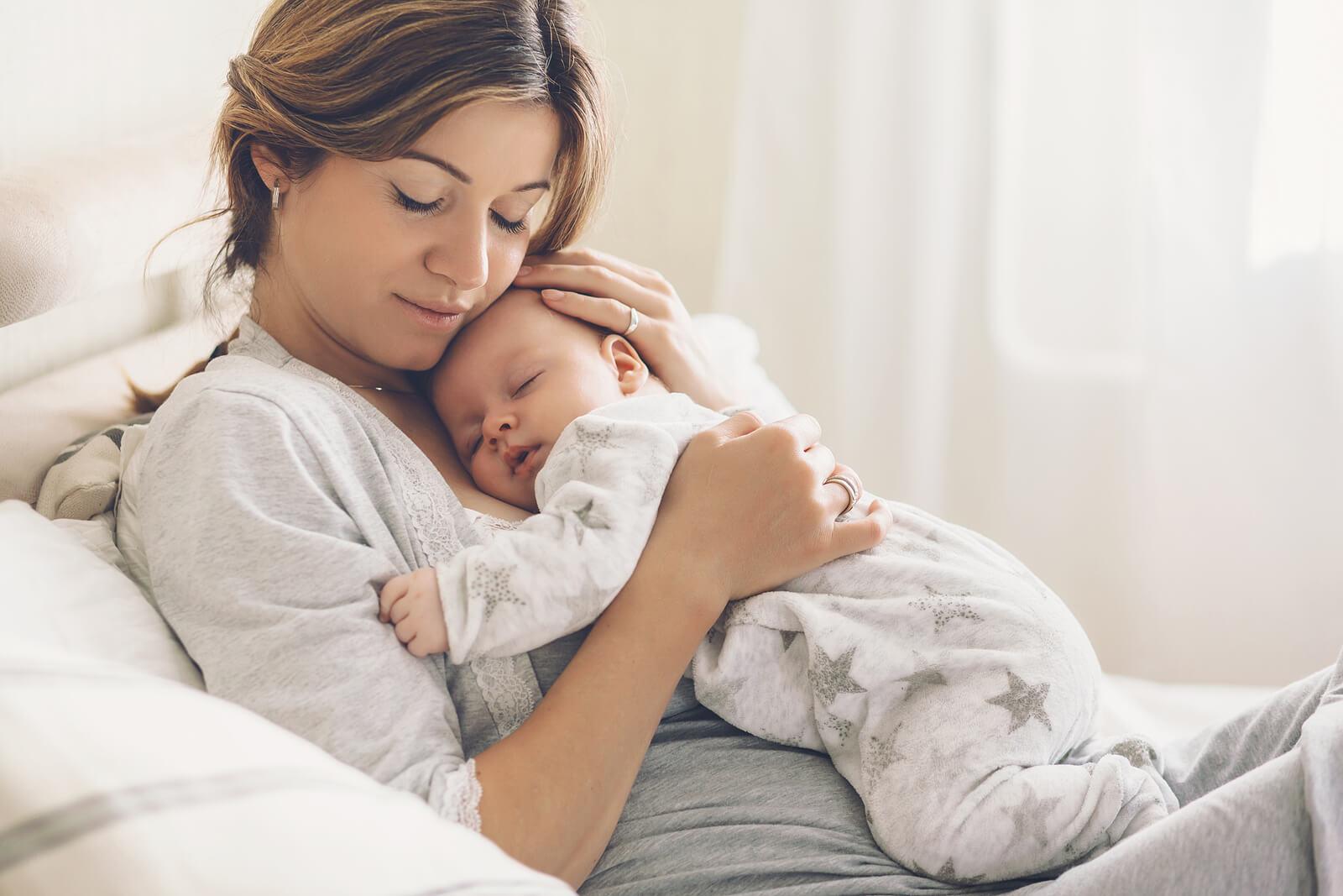 Madre abrazando a su bebé dormido en sus brazos.