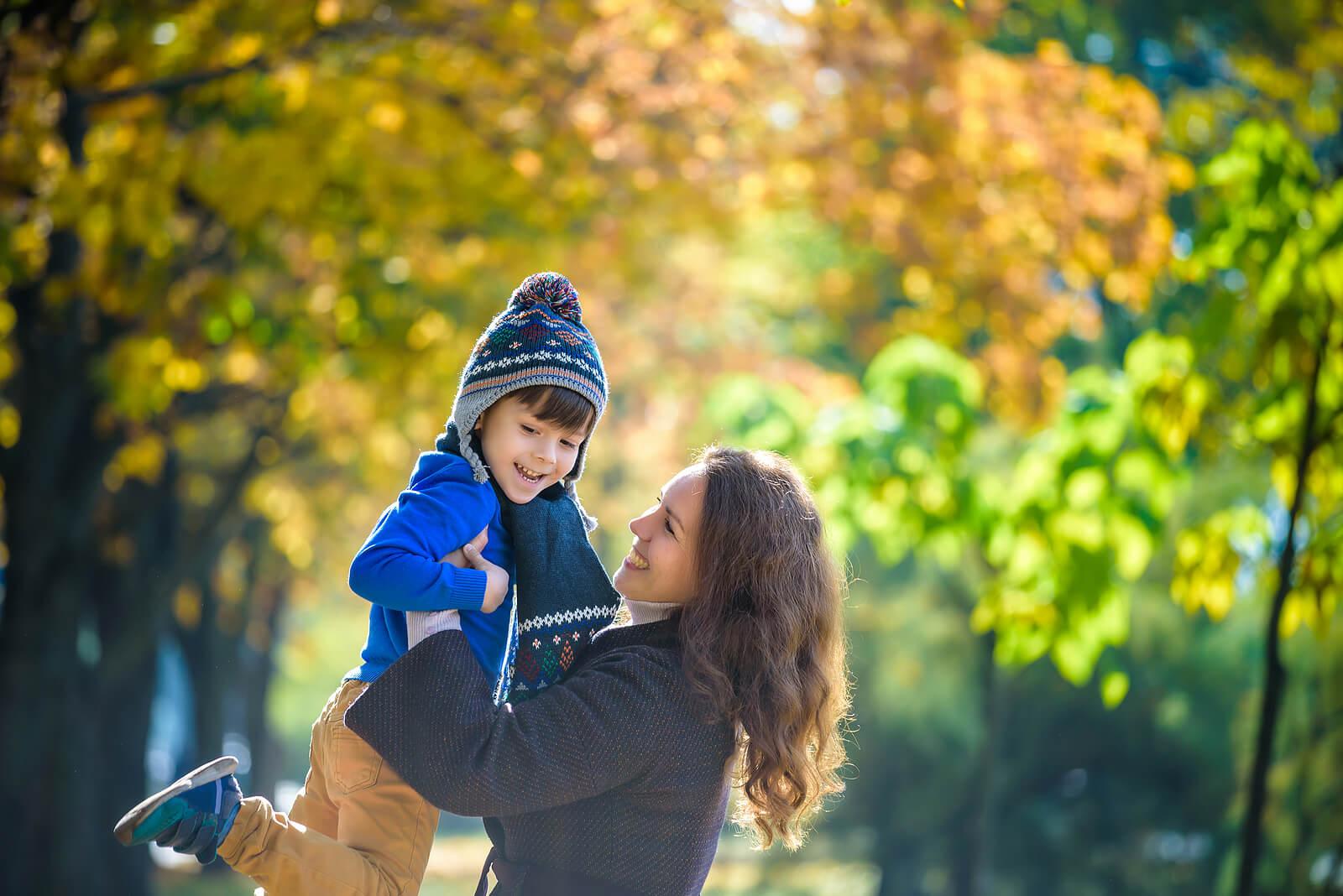 Madre jugando con su hijo en un parque en otoño.