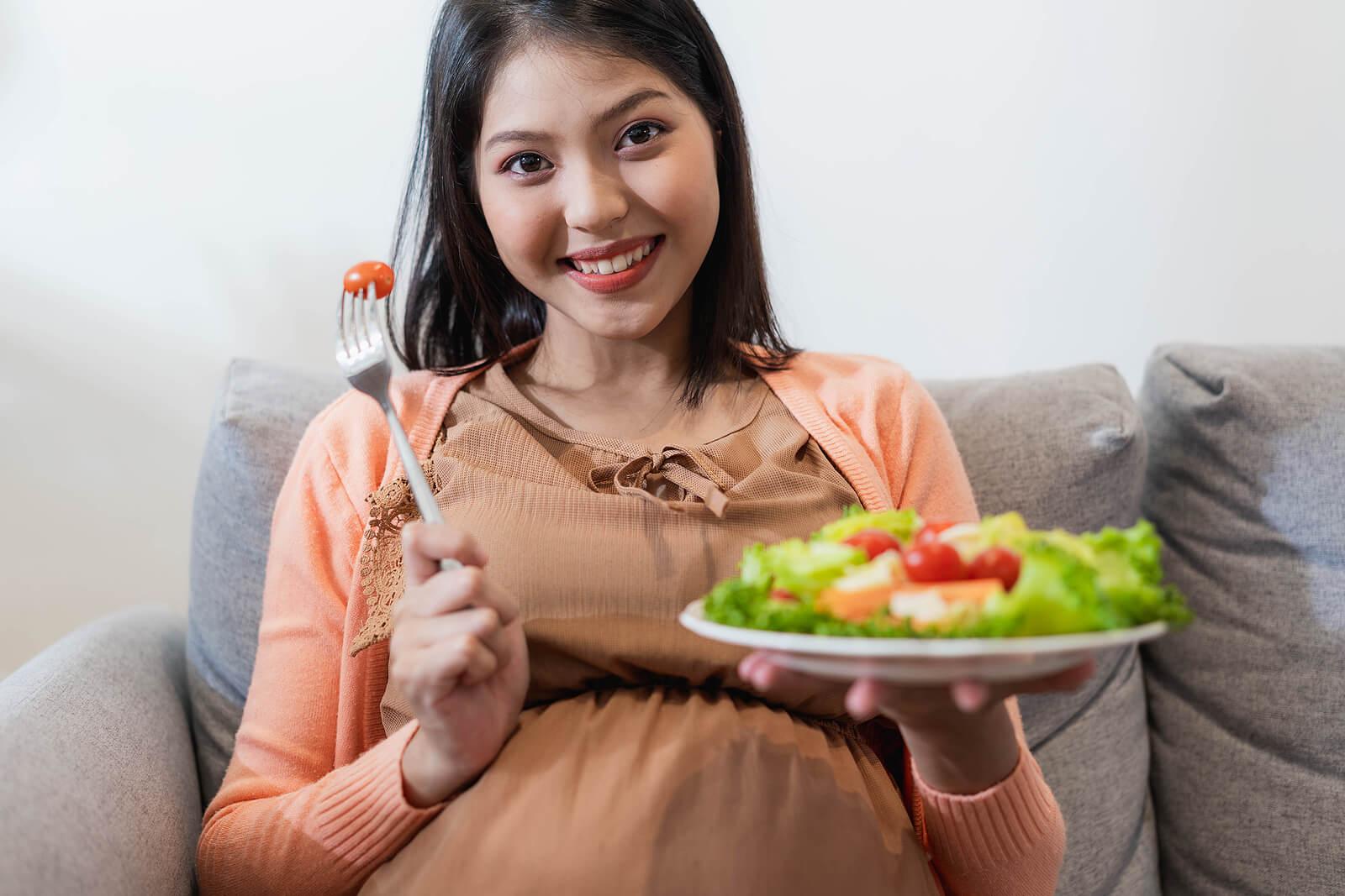 Mujer embarazada comiendo una ensalada.