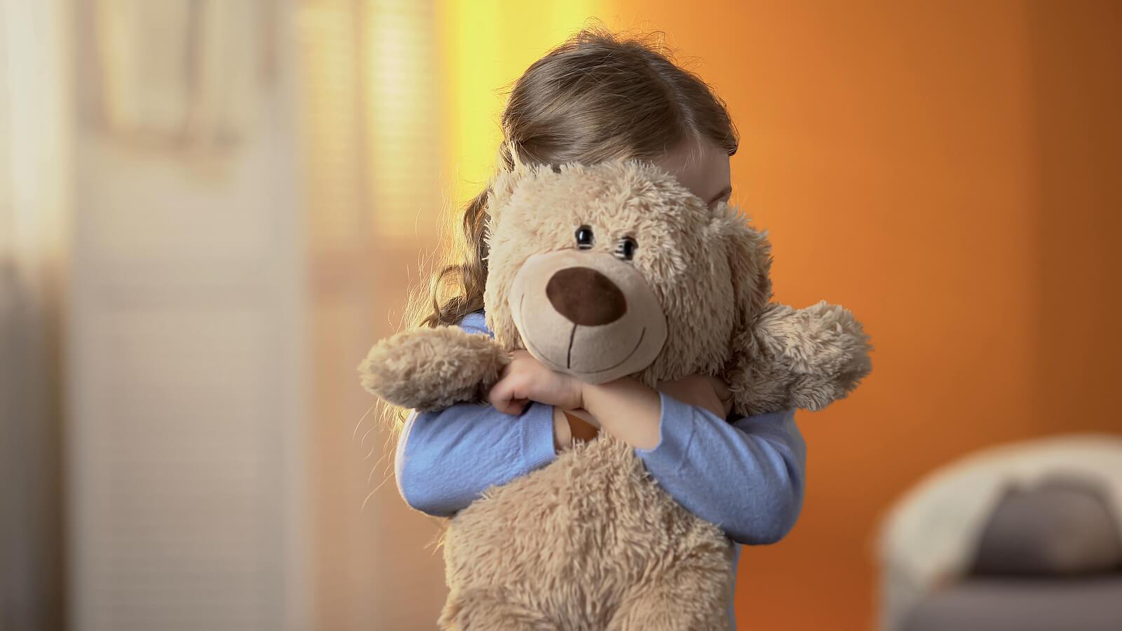 Niña abrazando un osito de peluche porque tiene miedo.