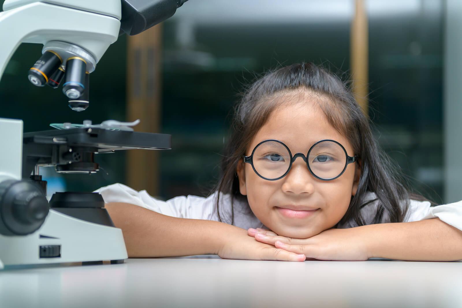 Niña científica junto a un microscopio.