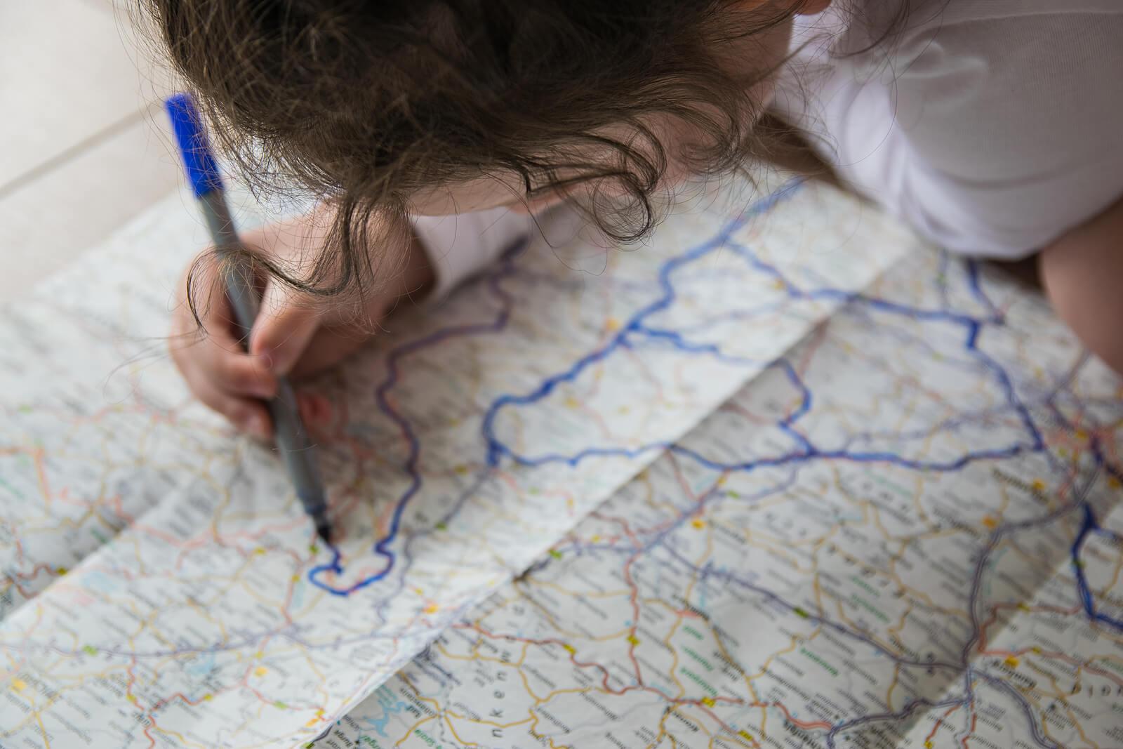 Niña trazando una ruta en un mapa.