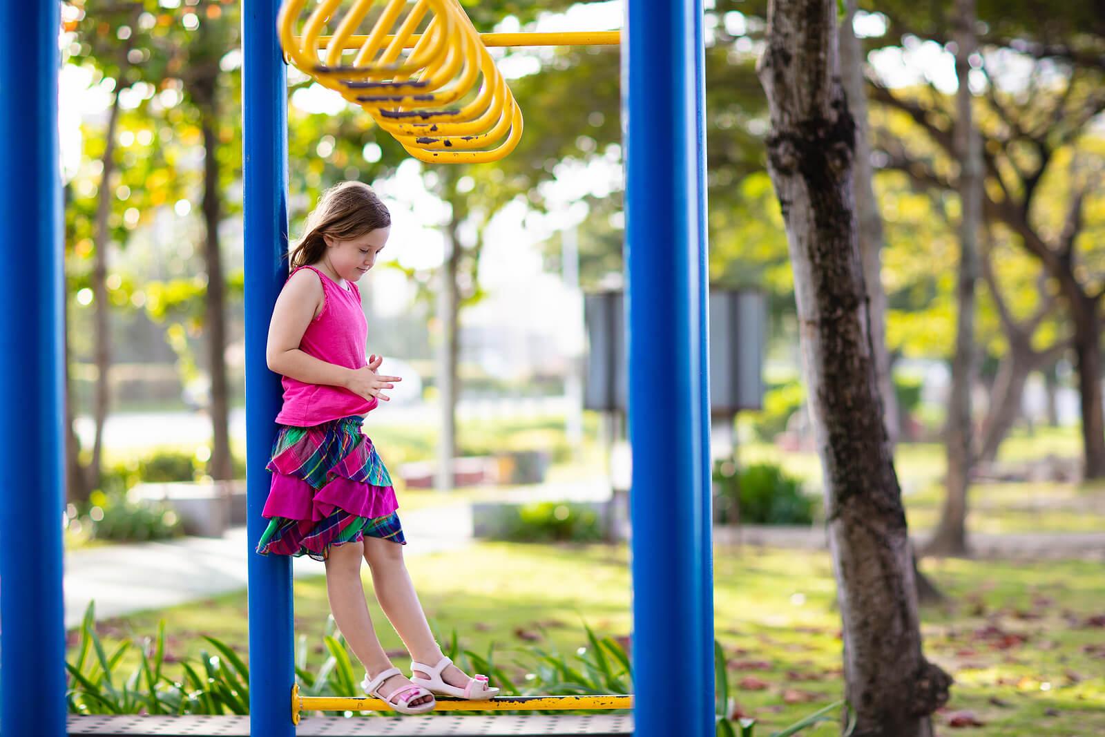 Niña jugando sola en el parque.