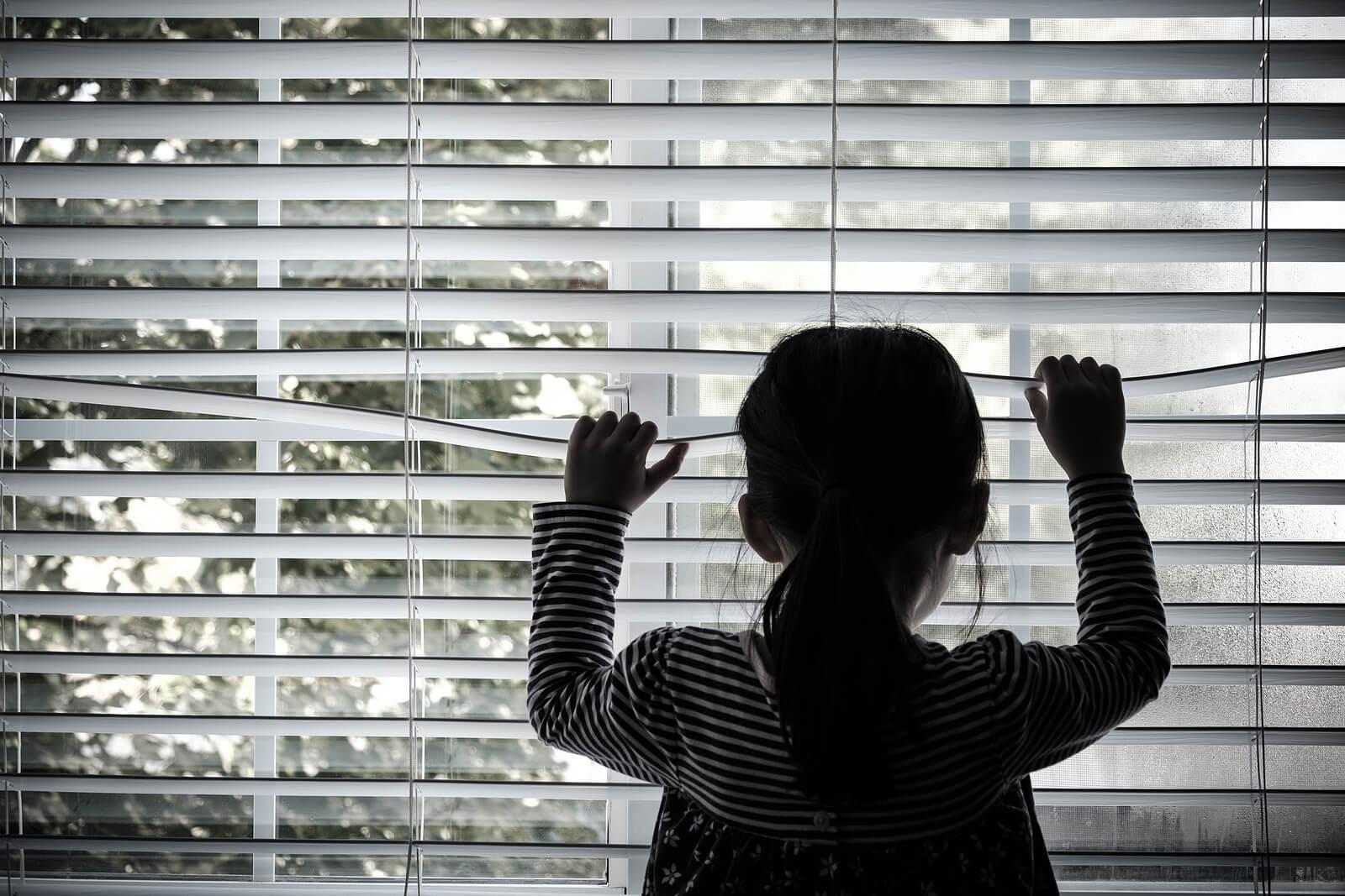Niña mirando por la ventana muy triste tras el abandono, una de las heridas emocionales de la infancia.
