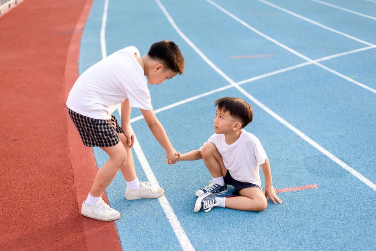 Niño ayudando a otro en la pista de atletismo gracias a la competitividad sana.