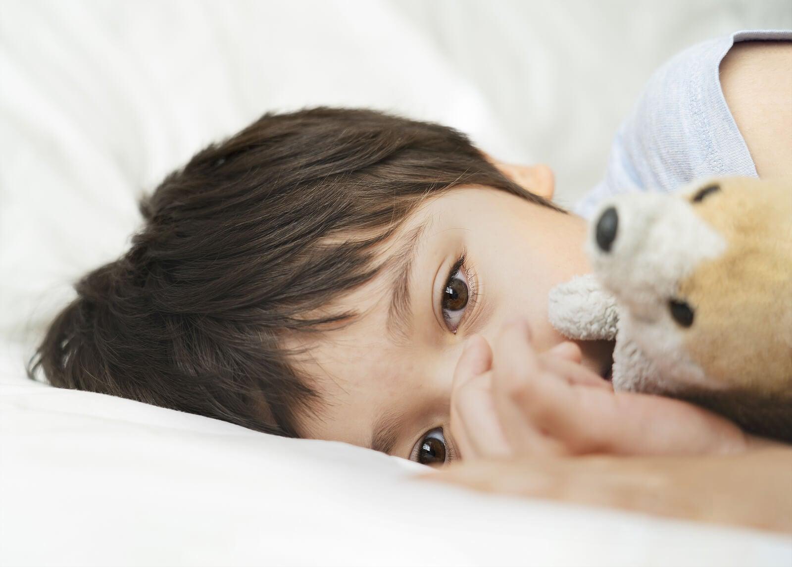 Con abrazado a su osito de peluche porque no puede dormir bien.