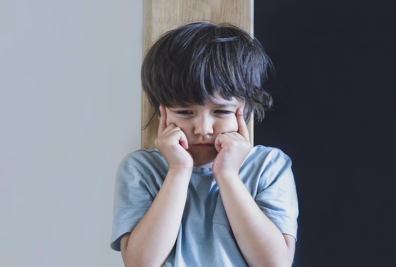 Niño enfadado con las manos en la cara.