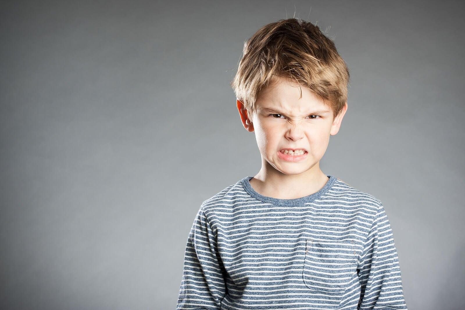 Niño enfadado porque desafía a sus padres y estos usan las estrategias.