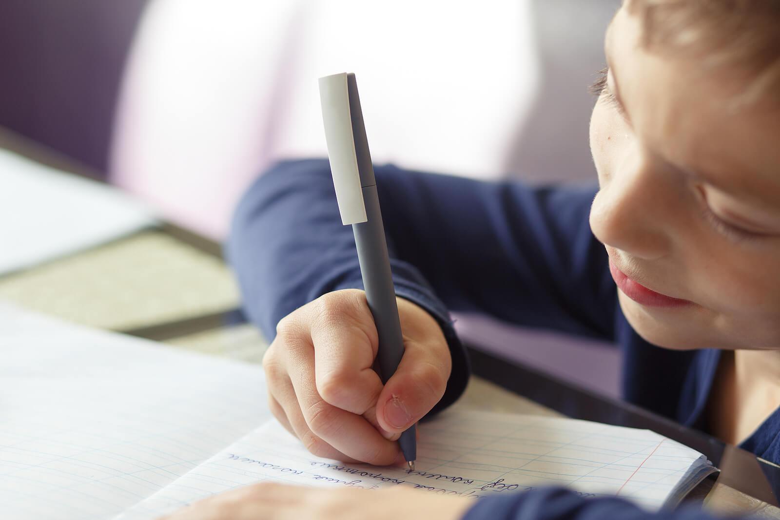 Niño aprendiendo a escribir a mano.