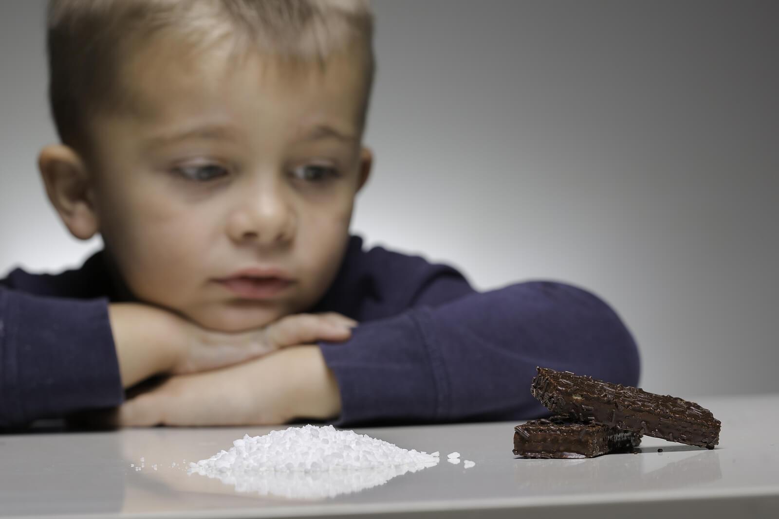 Niño mirando una montaña de azúcar y un trozo de chocolate.