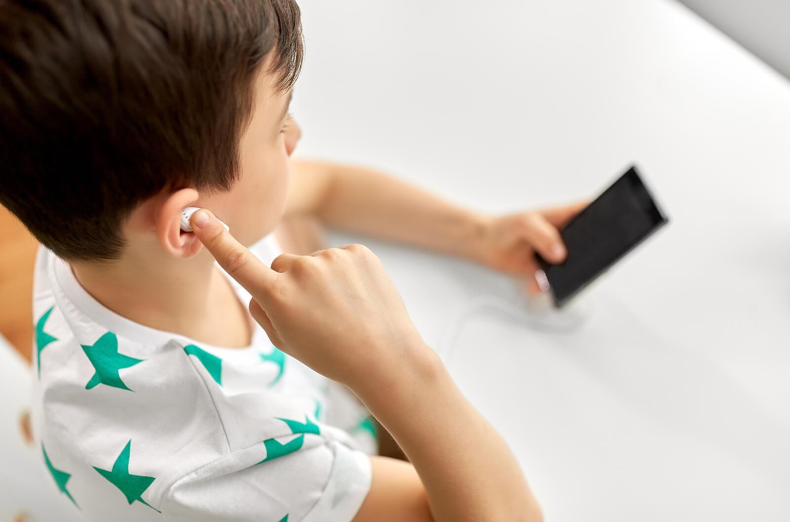 Niño escuchando un podcast en casa.