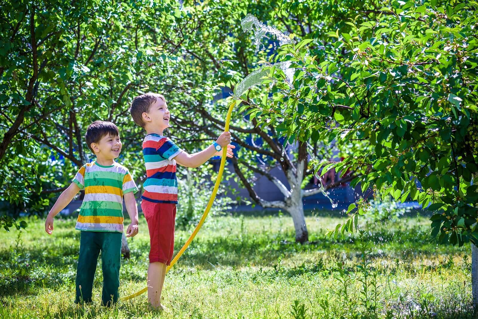 Niños regando los árboles y las plantas del jardín.