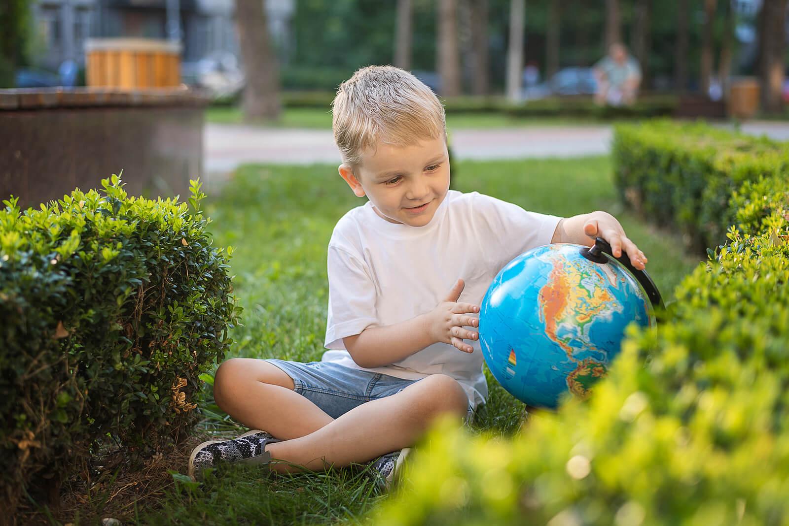 Niño aprendiendo a leer un globo terráqueo.