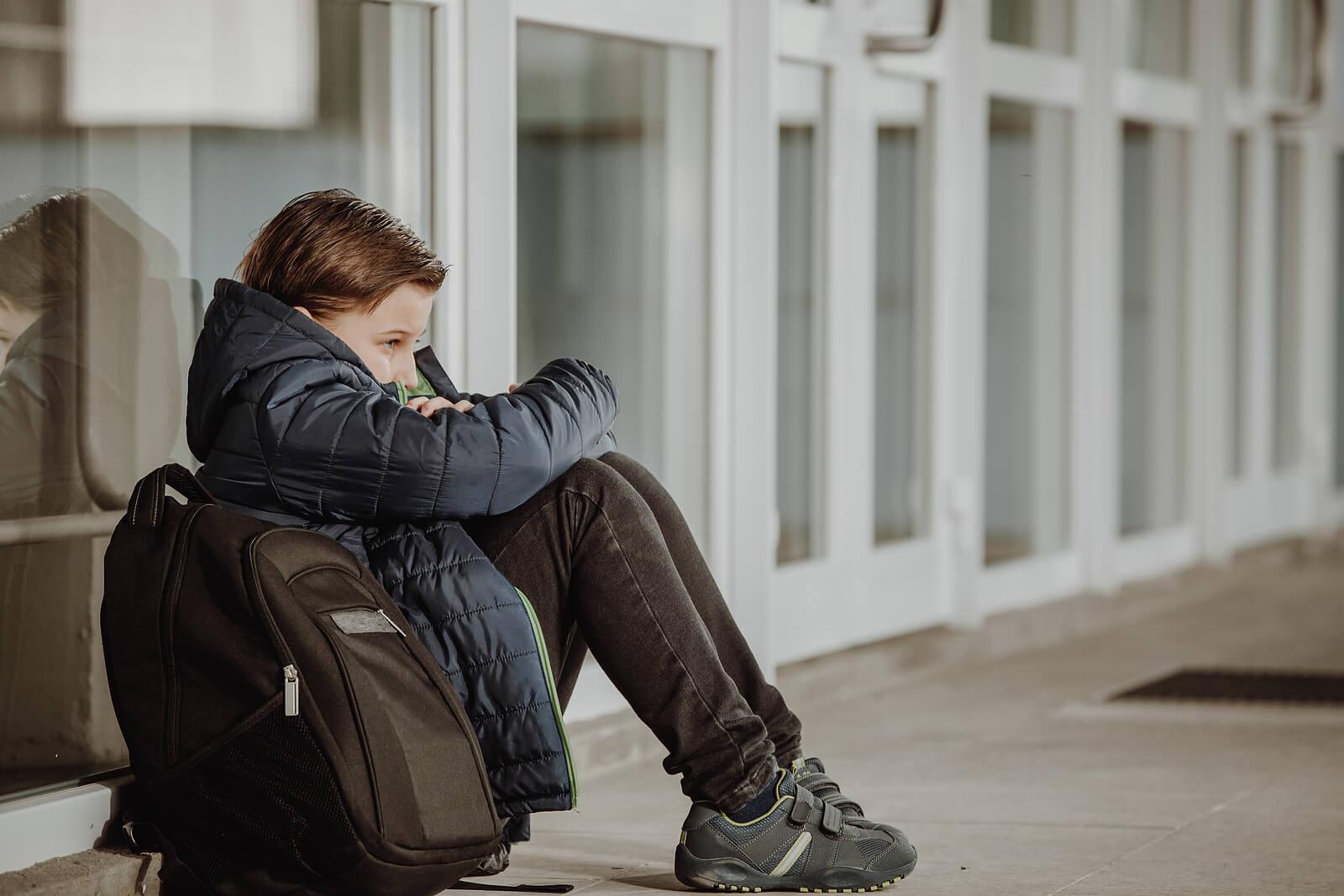 Niño triste porque está sufriendo novatadas en su nuevo colegio.