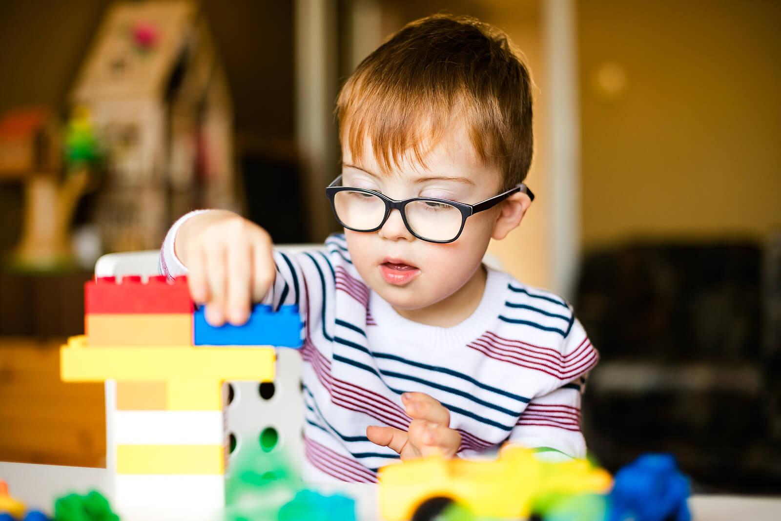 Niño con síndrome de Prader Willi jugando a las construcciones.