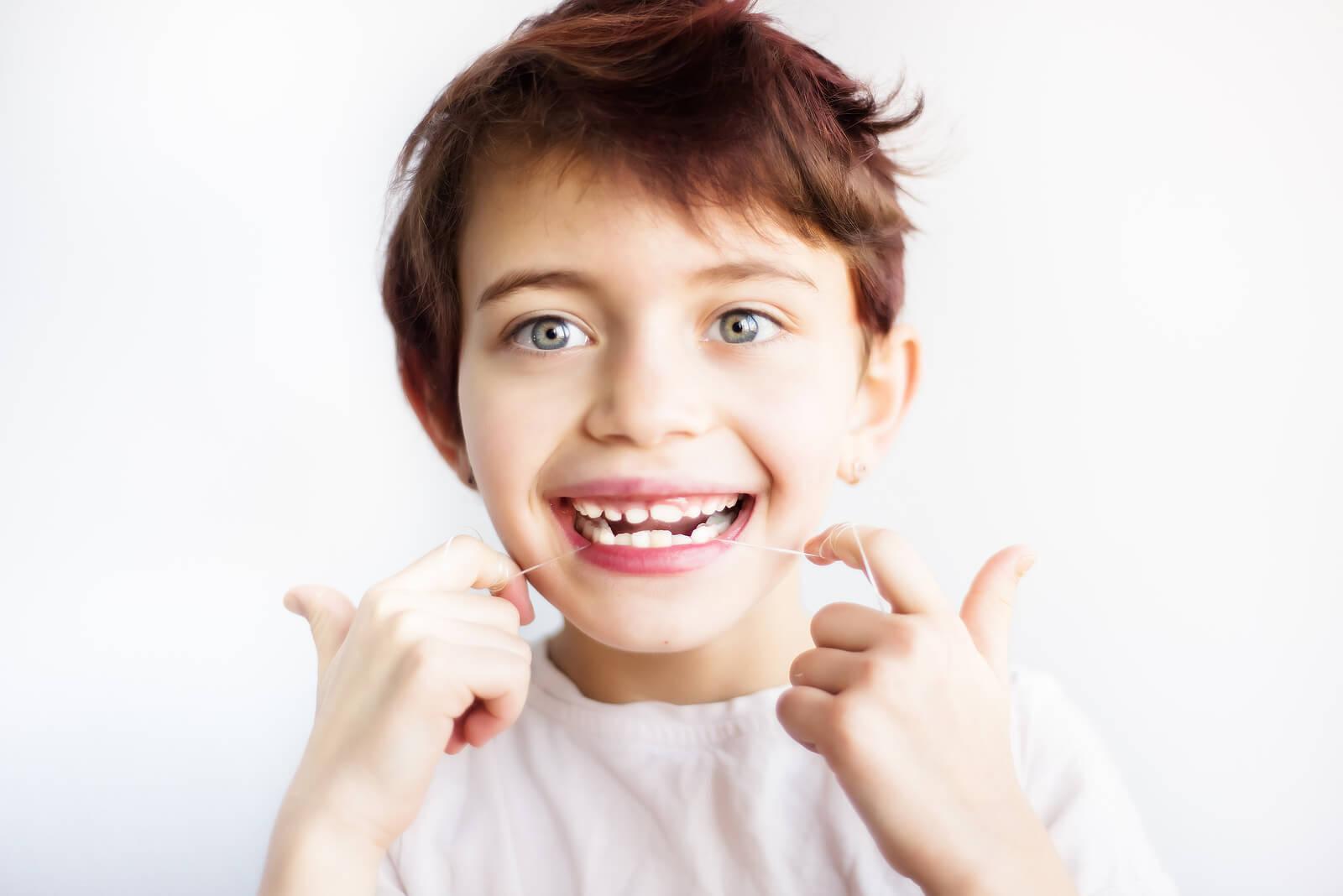 Niño utilizando hilo dental para la higiene bucal.