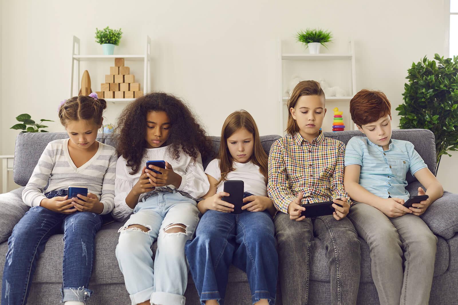 Niños sin hablar debido a que están mirando cada uno su teléfono móvil.