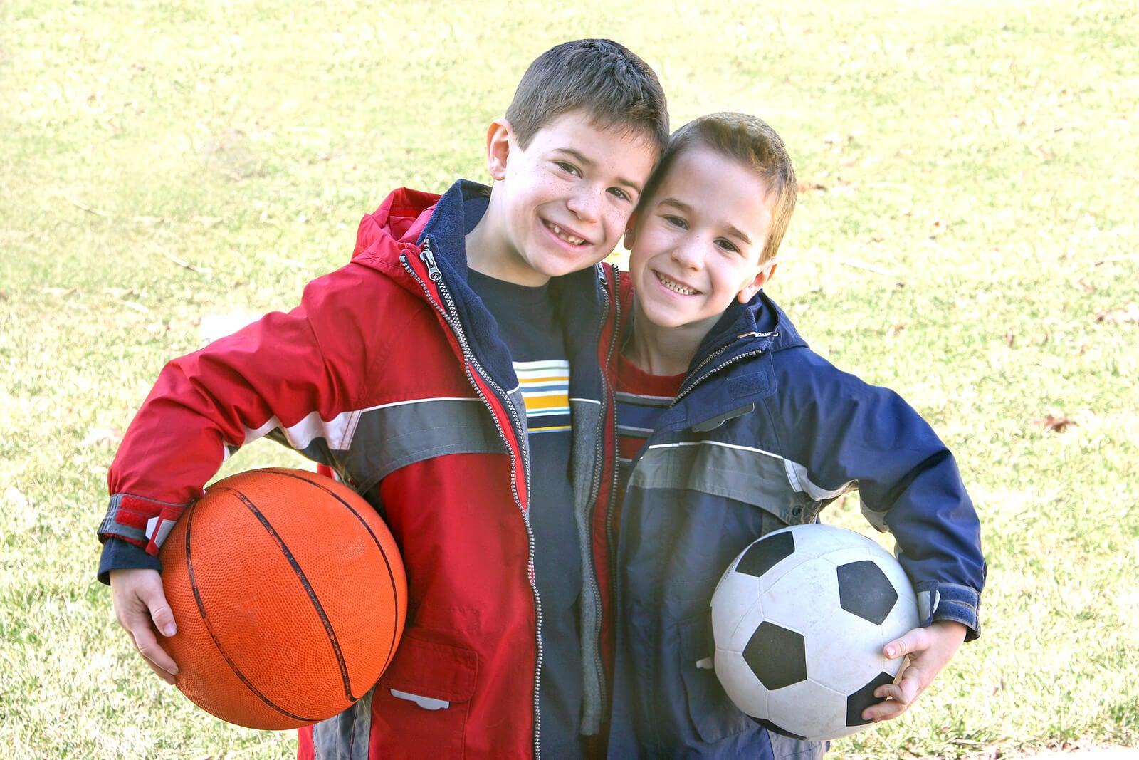 Amigos con una pelota de baloncesto y otra de fútbol.