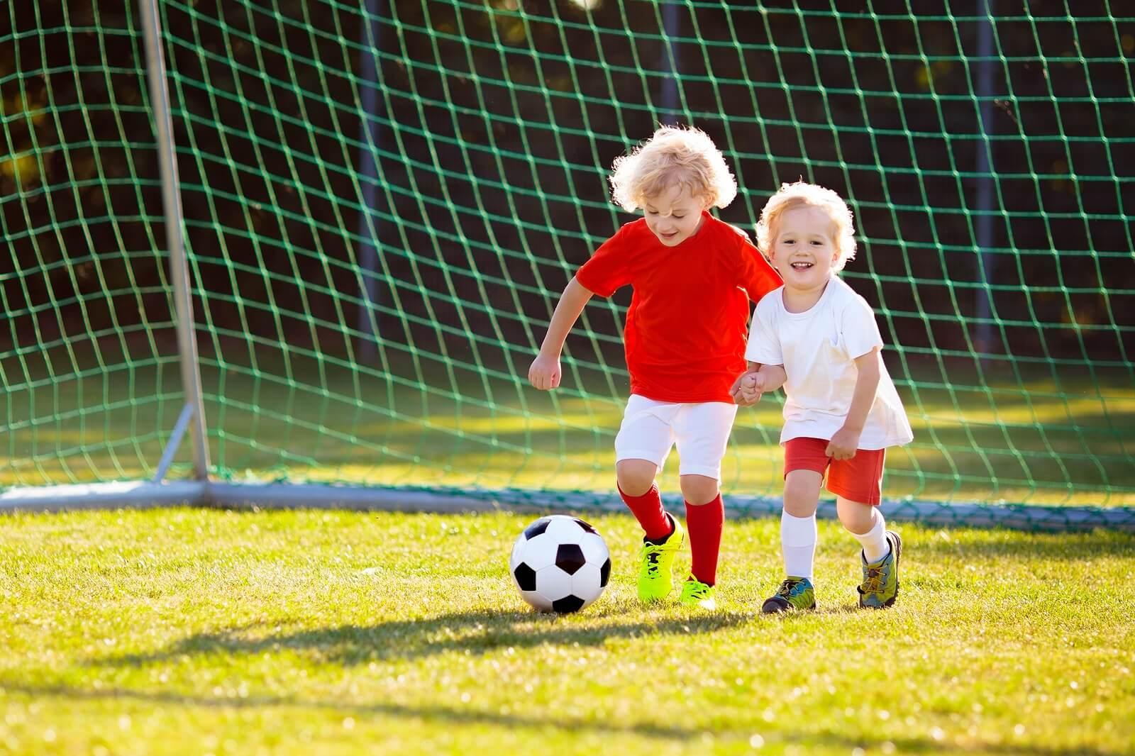 Niños felices jugando al fútbol porque sus padres tienen un papel importante en el deporte infantil.