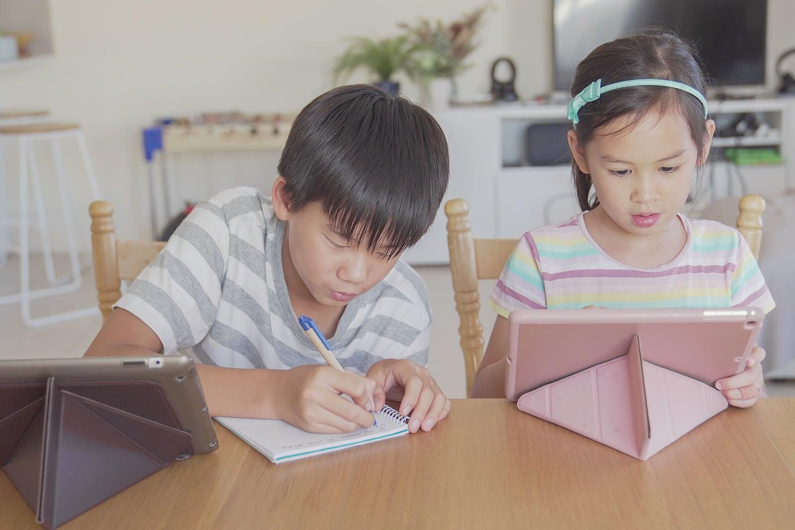 Niño haciendo deberes en casa mientras escuchan un podcast.