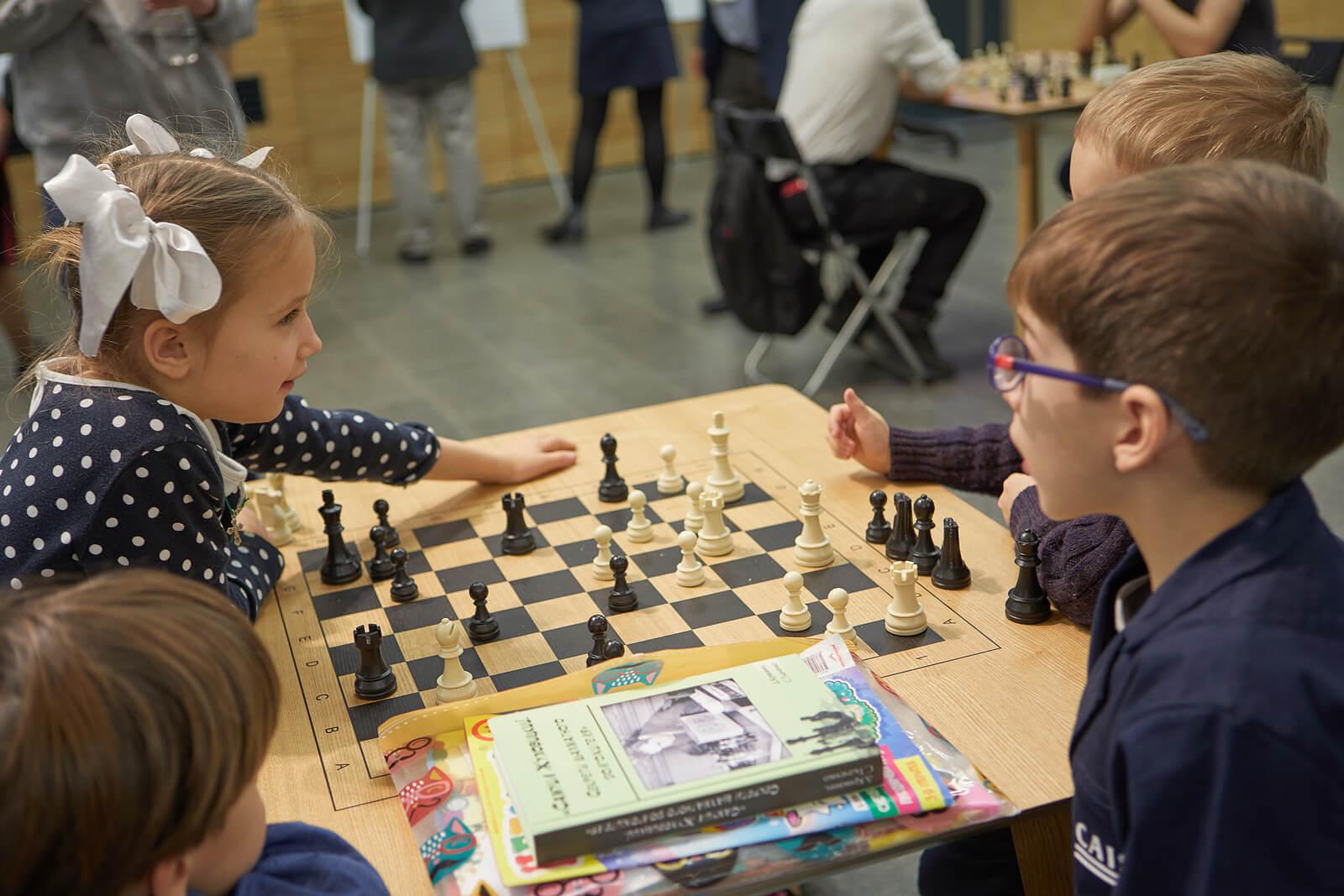 Niño jugando al ajedrez aprendiendo qué es la competitividad sana.