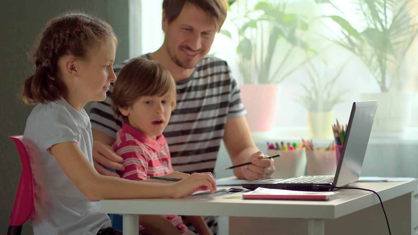 Padre ayudando a sus hijos a estudiar en casa.