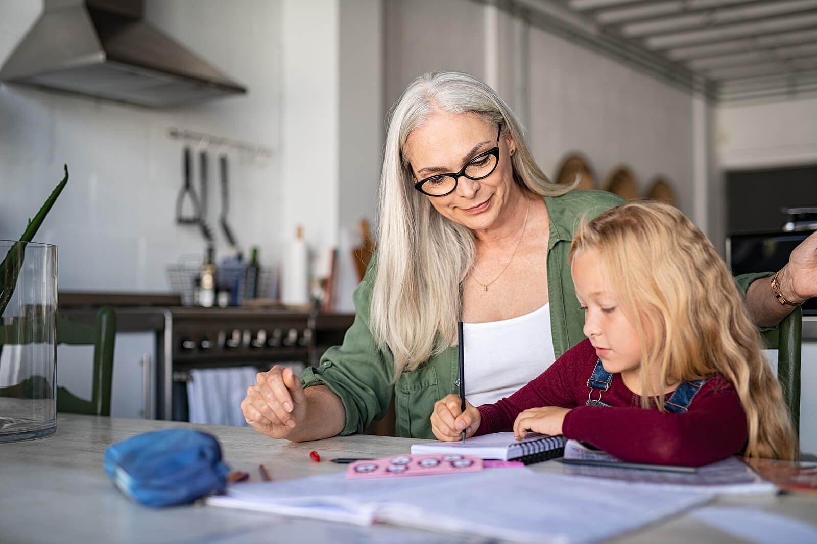 Abuela ayudando a su nieta a trabajar la expresión escrita.