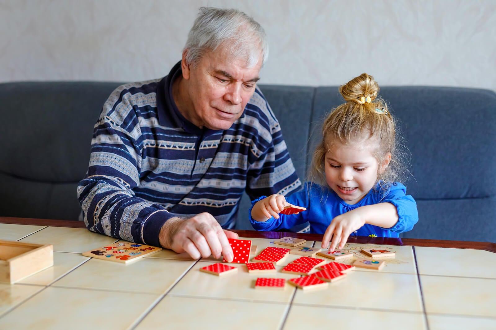 Abuelo con su nieta jugando a juegos para estimular la memoria de trabajo.