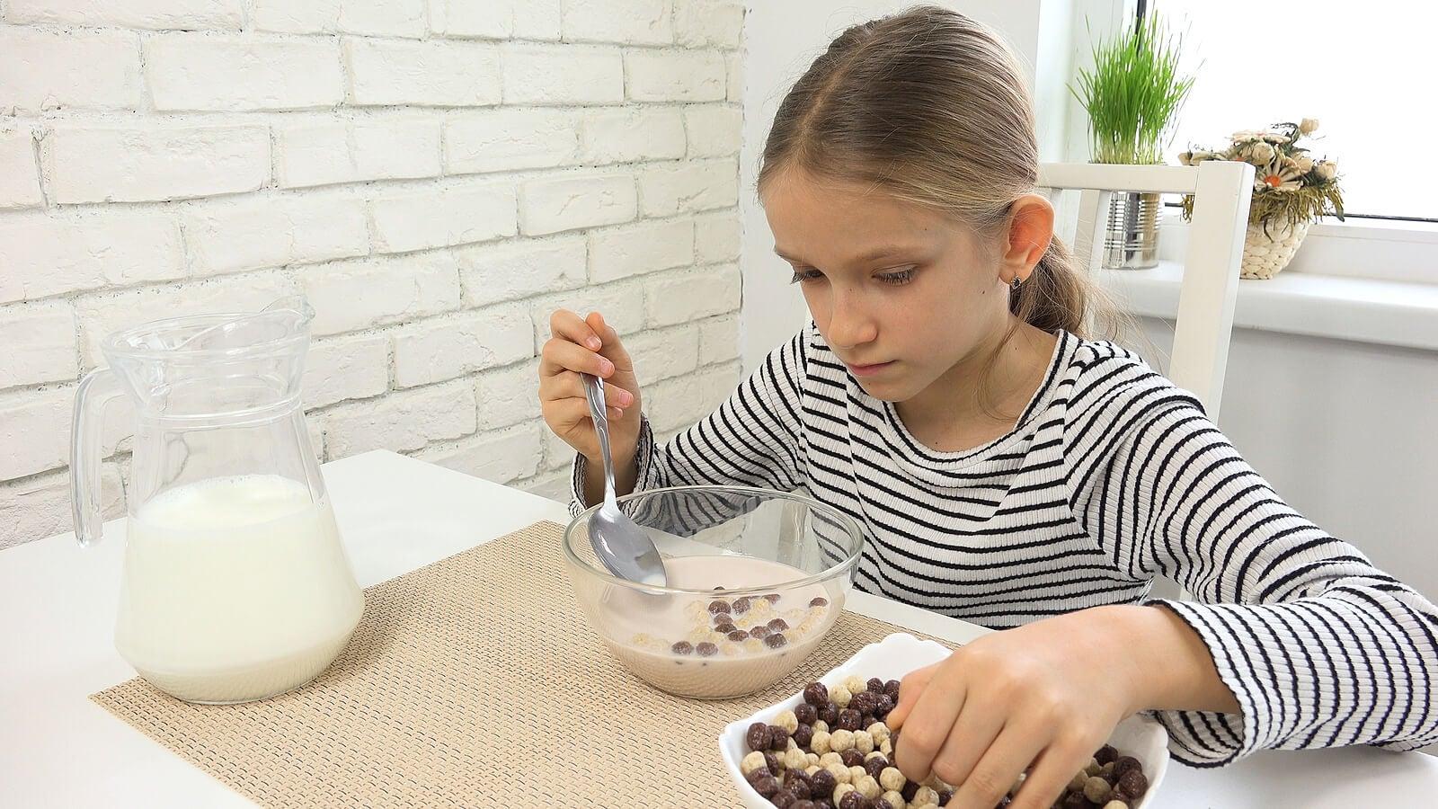 Adolescente desayunando cereales con cacao soluble.
