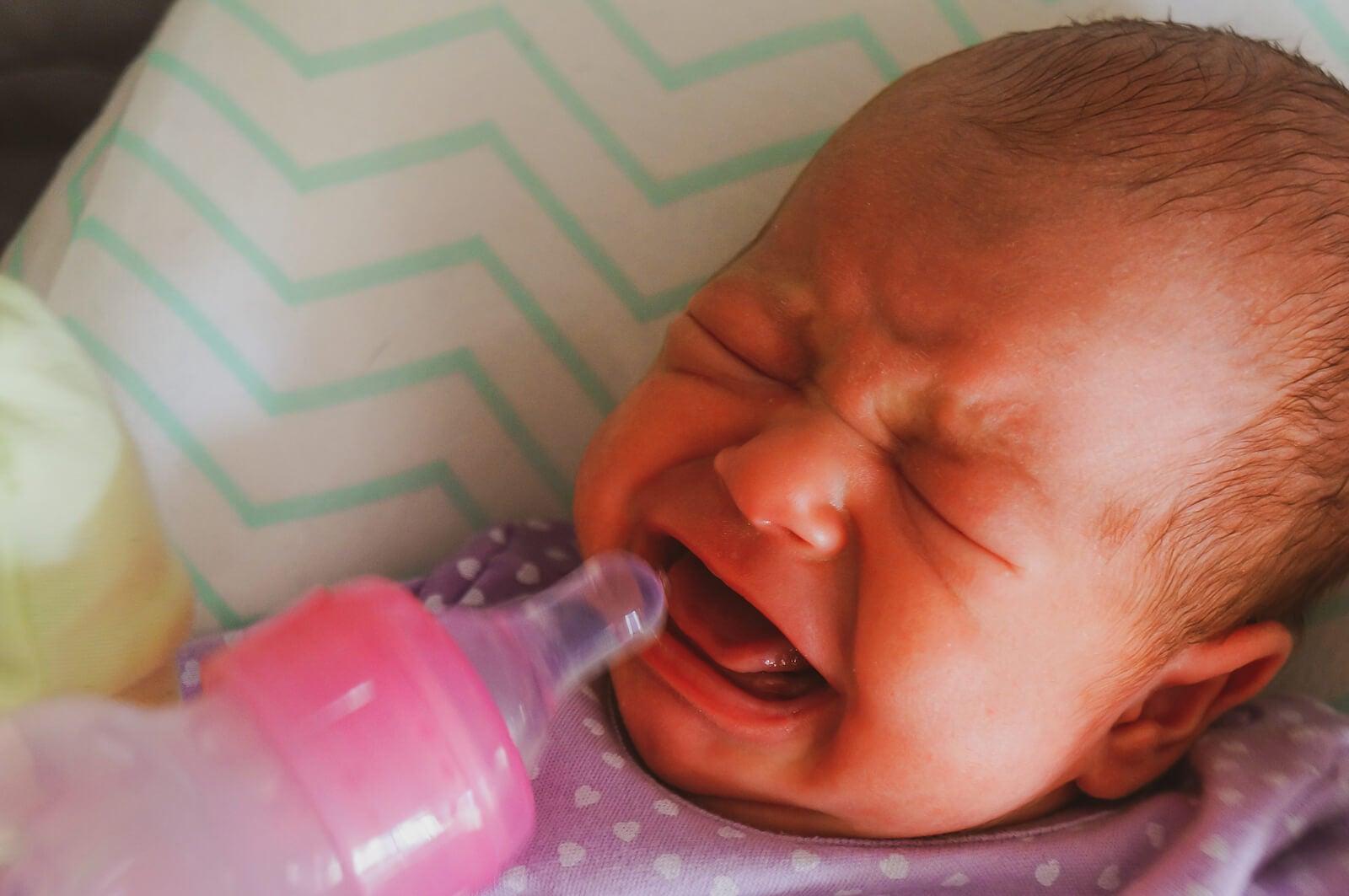 Bebé con síndrome de abstinencia neonatal llorando mientras come.