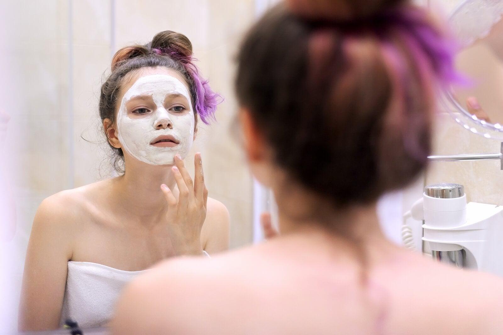 Chica aplicando una mascarilla facial para cuidar su piel en la adolescencia.